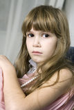 Sad girl with brown eys sitting on sofa Stock Image
