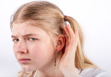 Sad girl can't hear. Young girl can't hear you - she cupping her hand behind her ear and looking very sadly Royalty Free Stock Photo