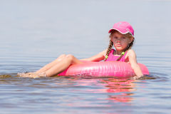 Sad girl in a cap floating in river sat on the swimming circle Royalty Free Stock Photos