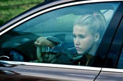 Sad girl in the car. Sad woman at driver seat in her car behind window full of rain drops stock photo