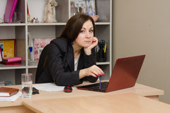 Sad girl at computer prints the document Stock Photo