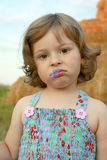 The sad girl with a cornflower in lips Royalty Free Stock Images