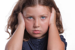 Sad Girl Covering Ears. A cute little girl with big blue eyes covers her ears while making a sad face Stock Image