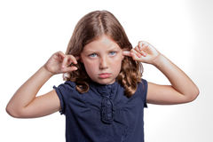 Sad girl covers ears. A cute little girl with big blue eyes covers her ears while making a sad face Stock Images