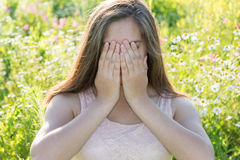 Sad girl covers face with her hands and weeps Stock Image