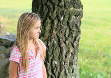 Sad girl. Cute little kid - sad girl in t-shirt with colorful stripes watching behind trunk of birch-tree Stock Image