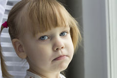 Sad girl. Distraught girl standing near the window Stock Photography