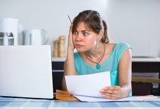 Sad girl with documents at kitchen Royalty Free Stock Image
