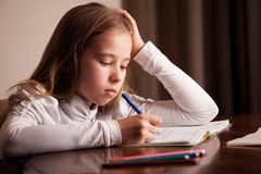 Sad girl doing homework Royalty Free Stock Photos