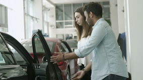 Sad girl don`t want to buy a car, which chose her boyfriend in car showroom. In love couple is choosing the automobile in car dealership. Young guy open the door stock video