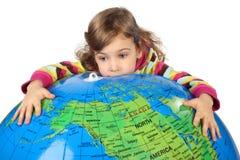 Sad girl embracing big inflatable globe Royalty Free Stock Images