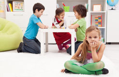 Sad girl feeling excluded from the group. Of playing kids Royalty Free Stock Image