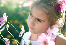Sad girl with flowers. A portrait of a sad or thoughtful young girl with flowers.  Narrow depth of field Royalty Free Stock Photos