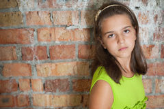 Sad girl in front of a brick wall Royalty Free Stock Photography