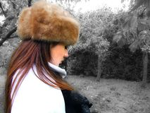 Sad girl in garden. A sad girl, with a fur hat, looks at the ground dejectedly in winter. The background has been digitally changed to black and white Stock Photo