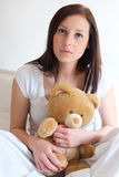 Sad girl getting lonely and hugging soft teddy bear Stock Images