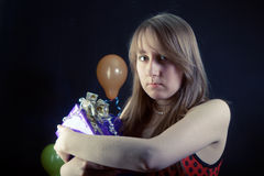 Sad girl with a gift box. On a dark background with balloons Royalty Free Stock Image