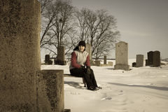 Sad girl in the graveyard Stock Image