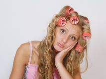 sad girl in hair curlers on long hair Stock Photos