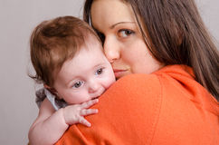 Sad girl on hands happy mom. Portrait of mother and baby at the hands of six mothers royalty free stock photo