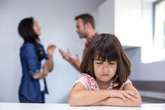 Sad girl hearing her parents arguing. In a kitchen Stock Photo