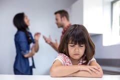Sad girl hearing her parents arguing Stock Photo