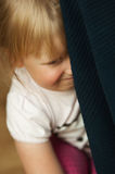 Sad Girl Hiding Behind Chair. A sad little girl hiding behind a stuffed chair ready to cry Royalty Free Stock Photos