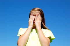 Sad Girl Hiding Face. A sad girl covering her sad face.  Trying to keep her sad face hidden Royalty Free Stock Images