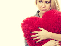 Sad girl holding big red pillow in heart shape Stock Photos