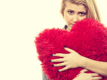 Sad girl holding big red pillow in heart shape Royalty Free Stock Photography