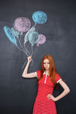 Sad girl holding drawn colorful balloons over blackboard background Stock Photos