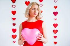 Sad girl holding heart balloon stock image