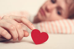 Sad girl is holding heart symbol by her finger Stock Photos