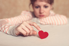 Sad girl is holding heart symbol by her finger. And looking at it. Love and relationships concept Royalty Free Stock Images