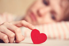 Sad girl is holding heart symbol by her finger Royalty Free Stock Image