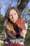 Sad girl holding red autumn leaf in her hand Stock Photo
