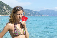 Sad girl holding a red heart on the seaside Royalty Free Stock Images