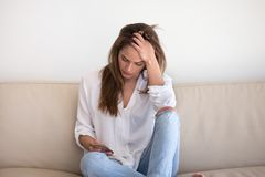 Sad girl holding smartphone waiting for message from boyfriend royalty free stock images