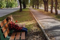 Sad girl with a lollipop in a autumn park. Royalty Free Stock Images