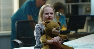 Sad girl in hospital. Sad girl in the hospital with a toy bear in her arms sad looking at the camera stock video footage
