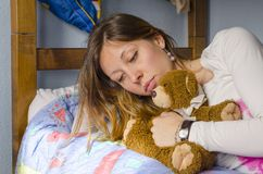 Sad girl hugging her toy bear Stock Image