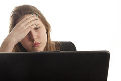Sad girl with laptop. Sad girl using a laptop to browse the net stock images