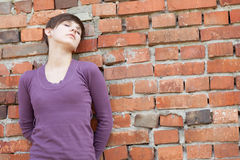 Sad girl leaning against wall Stock Photography