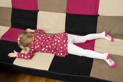 Sad girl is lieing on the sofa facedown Stock Image