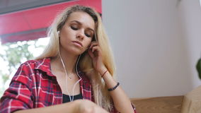 Sad girl listening to music on cellphone in cafe stock video
