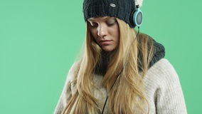 Sad girl listening to music on headphones winter in the winter stock video footage