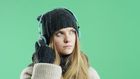 Sad girl listening to music on headphones winter in the winter stock footage