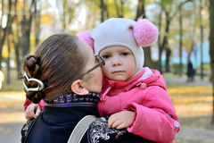 Sad girl. Little girl in a pink jacket and funny hat feels sad sitting on the hands of his mother. in a city park in the late autumn. mother calms her Royalty Free Stock Photography