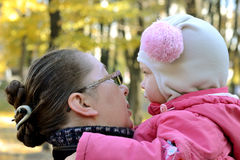 Sad girl. Little girl in a pink jacket and funny hat feels sad sitting on the hands of his mother. in a city park in the late autumn. mother calms her Stock Images