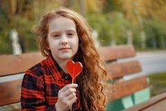 Sad girl with a lollipop in a autumn park. Stock Photos